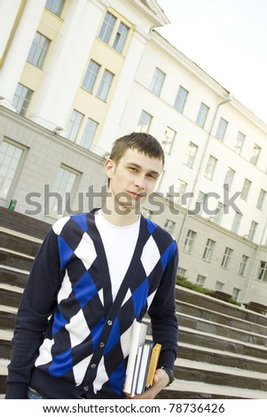 Closeup of an attractive male student on campus sits on the stairs with books - stock photo