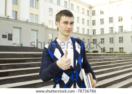 Closeup of an attractive male student on campus sits on the stairs with books. Thumbs up - stock photo