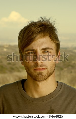 closeup of an attractive young man standing in a desert - stock photo