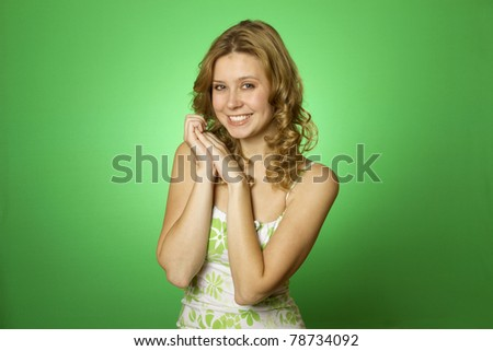 Closeup of an attractive young woman in a dress with a green background