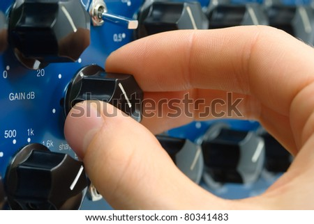 Closeup of an audio engineer's hand fine-tuning the sound on a knob - stock photo