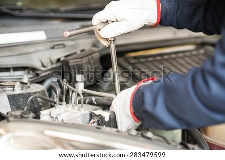 Closeup of an auto mechanic working on a car engine - stock photo