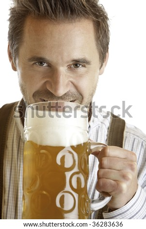 closeup of an Bavarian man which wants to drink out of Oktoberfest beer stein - stock photo