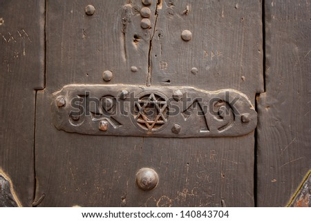 Closeup of an door with Star of David into a steel frame placed on textured colorful old wood.