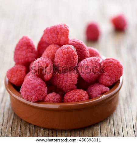 closeup of an earthenware bowl with a pile of appetizing ripe raspberries on a rustic wooden table - stock photo