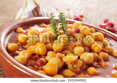 closeup of an earthenware bowl with potaje de garbanzos con jamon, a spanish chickpeas stew with ham - stock photo