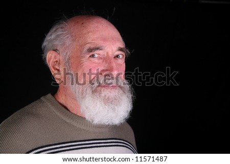 Closeup of an elderly grandfather isolated on black background - stock photo