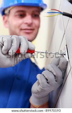 Closeup of an electrician at work - stock photo