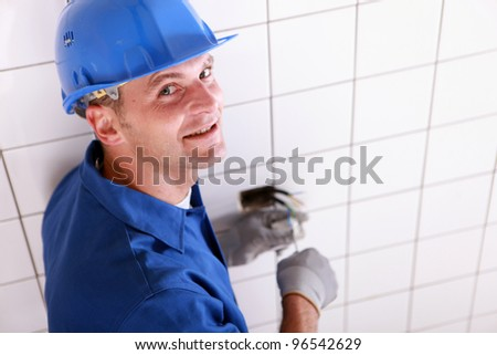 Closeup of an electrician at work - stock photo