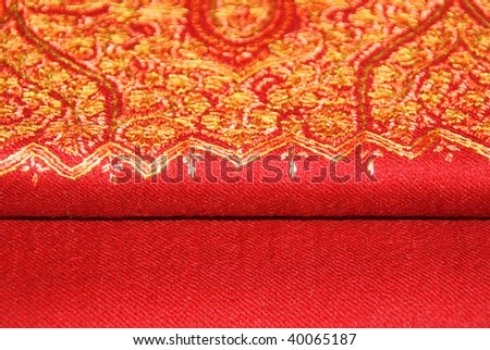 closeup of an elegant red pashmina shawl with delicate yellow embroidery - stock photo