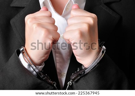 Closeup of an handcuffed businessperson in a black suit - stock photo