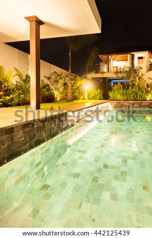 Closeup of an illuminated swimming pool with lights which belongs to fancy house or hotel at night - stock photo