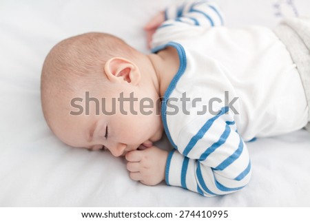 Closeup of an innocence baby boy sleeping and sucking his finger - stock photo
