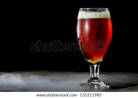 closeup of an irish red ale served in a chalice over a black background - stock photo