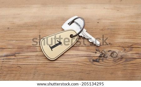 Closeup of an key of room number 1 with key on a wooden desk - stock photo