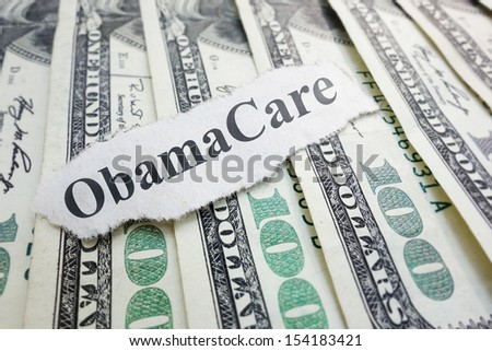 Closeup of an Obamacare newspaper headline on cash                               - stock photo