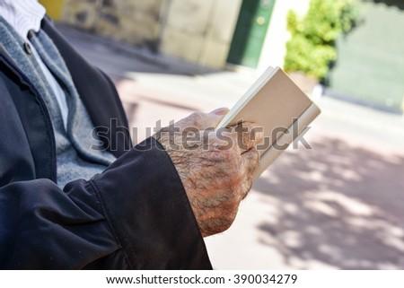 closeup of an old caucasian man reading a book outdoors - stock photo