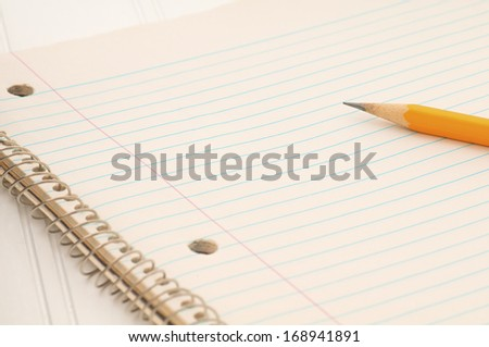 Closeup of an old Notebook of Off White, Lined Paper with part of a pencil showing with room or space for your words, text, or copy. - stock photo