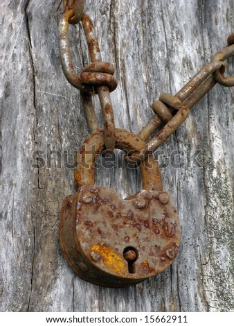 Closeup of an old padlock and rusty chain - stock photo