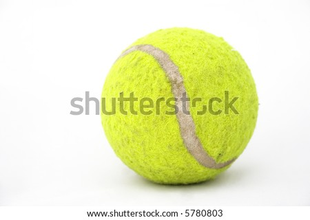 Closeup of an old tennis ball against a white background. This one is used as a dog toy.