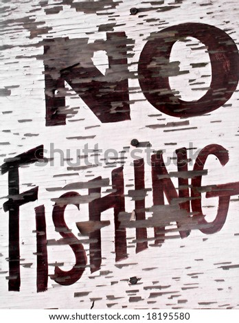 Closeup of an old vintage sign by a lake that reads NO FISHING. - stock photo