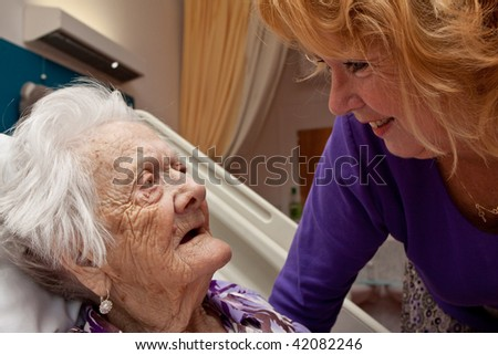 Closeup of an old woman with her daughter - stock photo