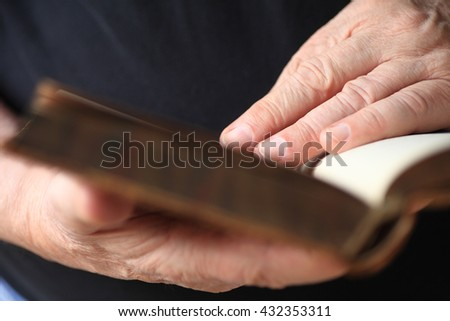 Closeup of an older man reading a vintage boo - stock photo