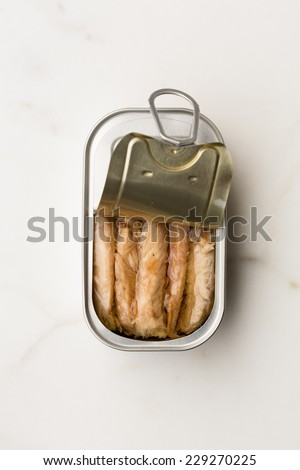 closeup of an open can of canned mackerel on a white marble background