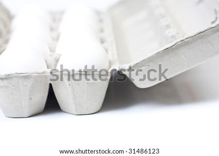 Closeup of an open carton of eggs, with selective focus on the front of the carton, isolated on white. - stock photo