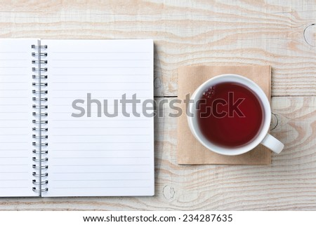Closeup of an open notebook and a cup of hot tea on a rustic white wood table. High angle shot in horizontal format. - stock photo
