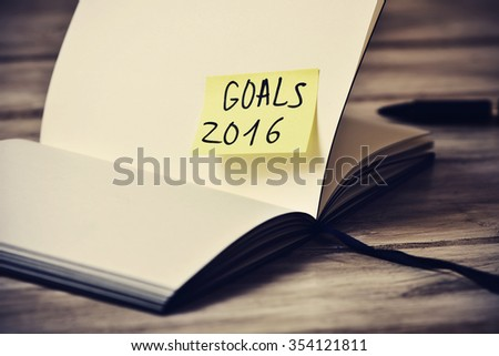 closeup of an open notepad with a yellow sticky note with the text goals 2016 stuck to one of its blank pages, with a filter effect