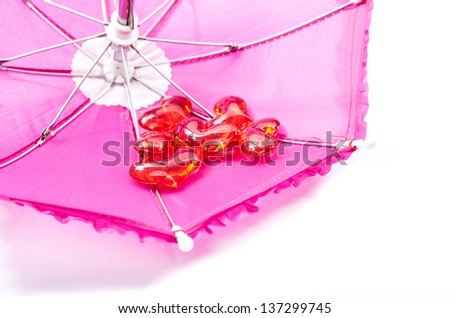 Closeup of an opened upside down vibrant pink umbrella with a cluster of romantic red hearts nestling inside conceptual of a Valentine or anniversary greeting card - stock photo