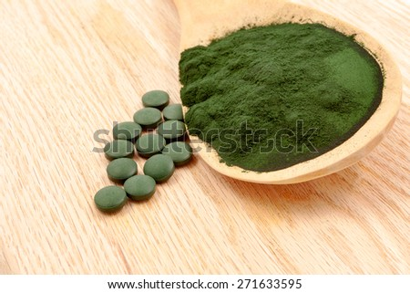 Closeup of an organic Spirulina algae powder and pills in a wooden spoon - stock photo