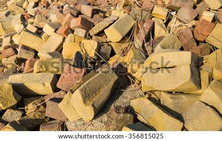 Closeup of an overgrown trash heap with the colorful misshapen bricks from a brick factory.