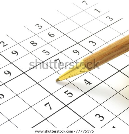closeup of an unfinished sudoku puzzle with brown pen - stock photo