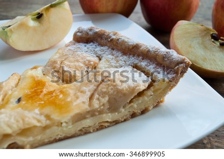 closeup of apple pie with raw apples on wooden table