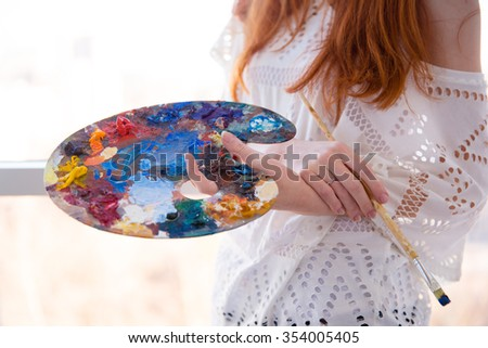 Closeup of art palette with oil paints and brush holded by young woman with red hair in white blouse - stock photo