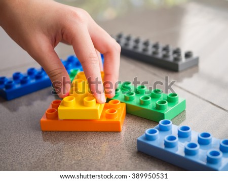 Closeup of asian kid's hand playing plastic  blocks, puzzle - stock photo