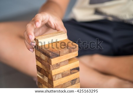 Closeup of asian kid's hand playing wood blocks stack game - stock photo