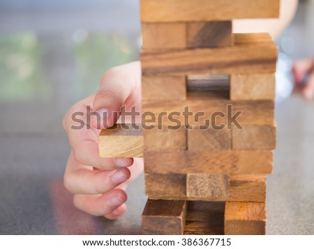 Closeup of asian kid's hand playing wood blocks stack game (jenga)