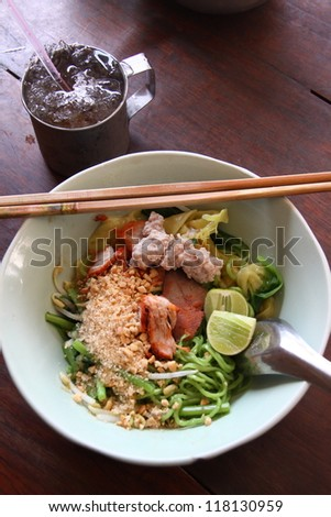 Closeup of asian stir fry with handmade green noodle, pork, vegetables, bean sprouts, and sesame seeds in a white bowl on wooden table. - stock photo