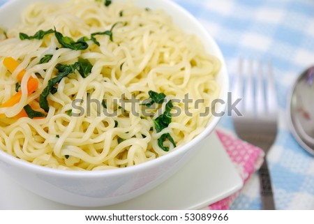 Closeup of Asian vegetarian yellow noodles with utensils and healthy vegetables. Suitable for concepts such as diet and slimming, healthy lifestyle, and food and beverage. - stock photo