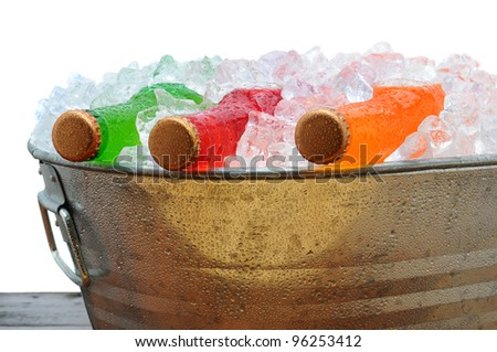 Closeup of assorted soda bottles in a metal party bucket filled with ice. - stock photo