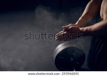 Closeup of athlete clapping hands before lifting barbells - stock photo