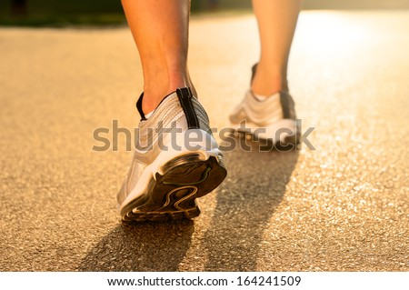 Closeup Of Athlete's Feet Running On Road  - stock photo