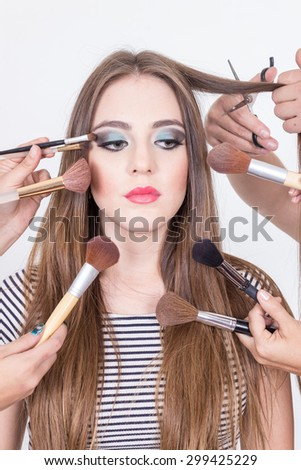 closeup of attractive blond girl getting hair and makeup done isolated over white - stock photo