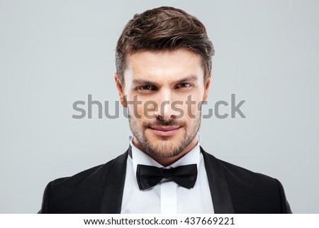 Closeup of attractive confident young man in tuxedo with bowtie - stock photo