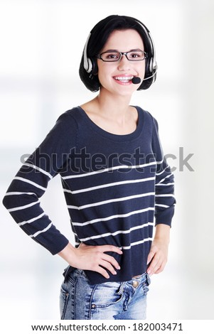 Closeup of attractive customer support representative smiling with headset - stock photo