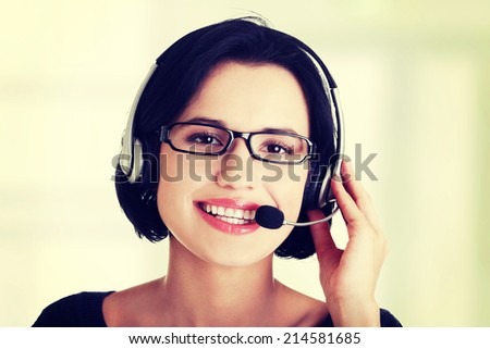 Closeup of attractive customer support representative smiling with headset on white background - stock photo