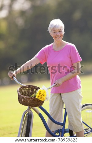 Closeup of attractive older lady on bicycle smiling for camera. - stock photo